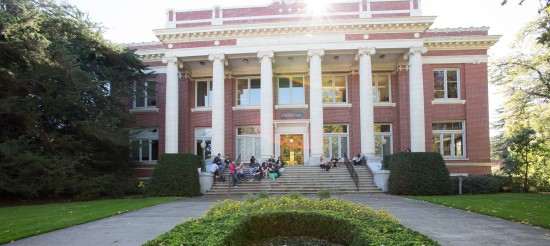 Students sit on the steps of Johnson Hall, a red brick building with white columns.