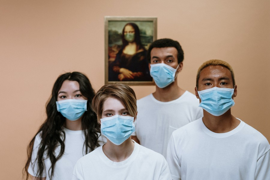 Young people wearing masks in front of a picture of the Mona Lisa, also wearing a mask.