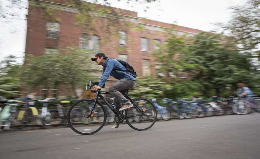 A young man bikes across the UO campus with a blurred background.