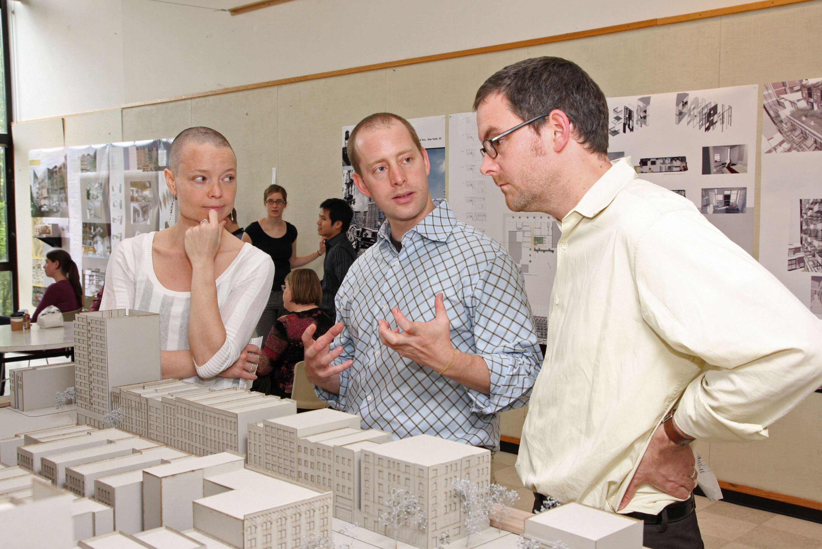 Faculty and students reviewing architectural designs and building models